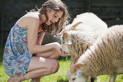 Germany, Bavaria, Young woman feeding sheep, portrait Stock Photos