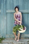 Germany, Bavaria, Woman in front of barn door holding basket with fresh - stock photo
