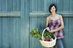 Germany, Bavaria, Woman standing in front of barn door, holding basket with - stock photo