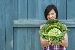 Germany, Bavaria, Woman holding savoy cabbage, smiling, portrait - stock photo