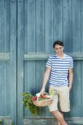 Germany, Bavaria, Man in front of barn door holding basket with fresh - stock photo