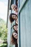 Germany, Bavaria, Four people standing next to barn door, smiling, portrait Stock Photos