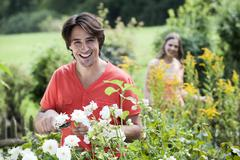 Germany, Bavaria, Man pruning flowers, woman in background, smiling, portrait - stock photo
