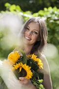 Germany, Bavaria, Woman holding bunch of sunflowers, smiling, portrait - stock photo