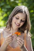 Germany, Bavaria,  Woman plucking petals from flower - stock photo