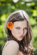 Germany, Bavaria, Woman with flower in hair, pouting lips, portrait, close-up Stock Photos