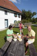 Germany, Bavaria, Two men at table in garden preparing food - stock photo