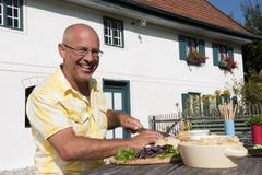 Germany, Bavaria, Man at table in garden preparing food, smiling, portrait - stock photo