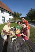 Germany, Bavaria, People at table in garden preparing food - stock photo
