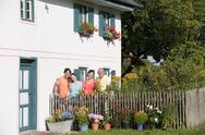 Stock Photo of Germany, Bavaria, Four persons standing at garden fence, portrait
