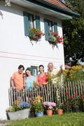 Germany, Bavaria, Four persons standing at garden fence, portrait Stock Photos
