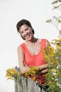 Germany, Bavaria, Woman leaning against garden fence, arms crossed, smiling, Stock Photos