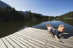 Italy, South Tyrol, Couple sunbathing in chairs on jetty - stock photo