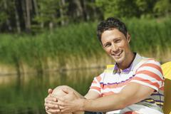 Italy, South Tyrol, Man sitting in chair by lake, portrait - stock photo