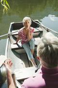 Italy, South Tyrol, Senior couple in rowing boat, senior woman blowing a kiss, Stock Photos