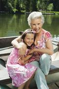 Italy, South Tyrol, Grandmother and granddaughter (8-9) sitting in rowing boat, - stock photo