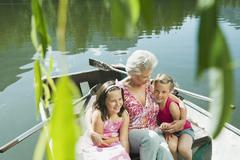 Italy, South Tyrol, Grandmother and grandchildren (6-7) (8-9) sitting in rowing Stock Photos