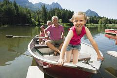 Italy, South Tyrol, Grandparents and children (6-7) (8-9) in rowing boat on Stock Photos