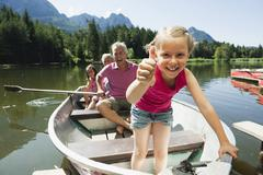 Stock Photo of Italy, South Tyrol, Grandparents and children (6-7) (8-9) in rowing boat on