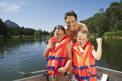 Italy, South Tyrol, Father and children (6-7) (8-9), wearing life jackets, Stock Photos