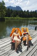 Italy, South Tyrol, Women sitting in deck chair on jetty, smiling, portrait - stock photo