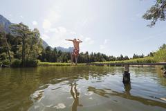 Italy, South Tyrol, Senior man jumping into lake, rear view Stock Photos