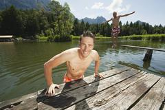 Italy, South Tyrol, Man in foreground leaning on jetty, senior man in background Stock Photos