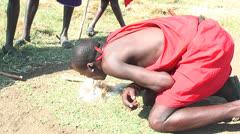 Masai warrior making fire in Manyatta in Kenya Stock Footage