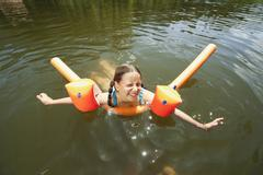 Italy, South Tyrol, Girl (8-9) swimming in lake, smiling, portrait - stock photo