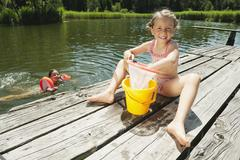 Italy, South Tyrol, Girl (6-7) playing with net and bucket on jetty, girl (8-9) Stock Photos