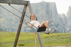 Italy, Seiseralm, Girl (6-7) sitting on swing, portrait Stock Photos