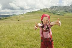 Italy, Seiseralm, Girl (8-9) in meadow giving thumbs up, smiling, portrait Stock Photos