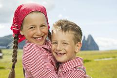 Italy, Seiseralm, Boy (6-7) and girl (8-9) in field, embracing, smiling, Stock Photos