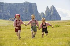 Italy, Seiseralm, Three children (4-5), (6-7), (8-9) running in field Stock Photos