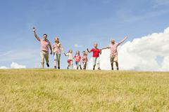 Italy, Seiseralm, Family walking in field, cheering Stock Photos