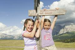 Italy, Seiseralm, Girls (6-7), (8-9) standing by sign post, smiling, portrait - stock photo