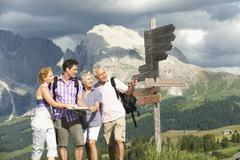 Italy, Seiseralm, Four persons standing next sign post Stock Photos