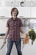 Germany, Berlin, Young man in kitchen holding bunch of carrots and knife, - stock photo