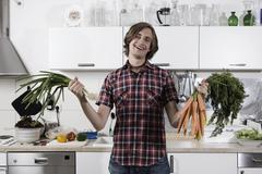 Germany, Berlin, Young man in kitchen holding bunch of carrots and spring - stock photo