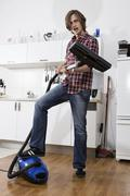 Germany, Berlin, Young man with vacuum cleaner, portrait - stock photo