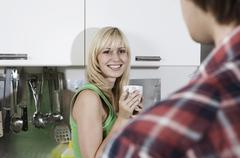 Germany, Berlin, Young couple in kitchen, smiling, portrait - stock photo