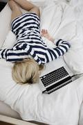 Germany, Berlin, Young woman lying in bed, laptop beside, elevated view - stock photo