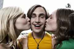 Germany, Berlin, Two young women kissing man on cheek, laughing, portrait, - stock photo