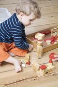 Germany, Berlin, Boy (3-4) playing with building bricks - stock photo