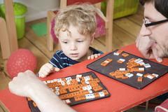 Germany, Berlin, Father and son (3-4) playing with toy tiles - stock photo