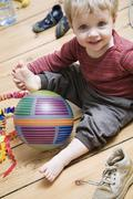 Germany, Berlin, Boy (2-3) sitting on wooden floor, playing with his ball, Stock Photos
