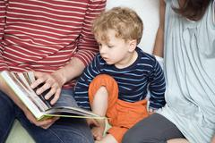 Germany, Berlin, Parents and son (3-4) reading a book, close-up - stock photo