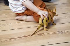 Germany, Berlin, Child playing with toy dinosaur - stock photo