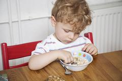 Germany, Berlin, Boy (3-4) sitting at table, playing with food, looking down, Stock Photos