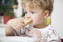 Germany, Berlin, boy (3-4) eating bread roll, portrait - stock photo